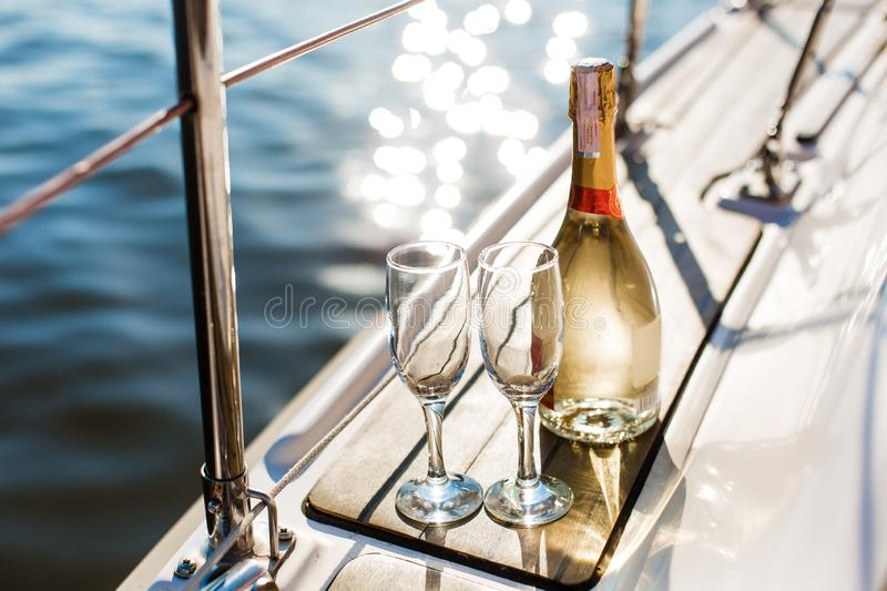 Empty glasses and bottle with champagne with sea background royalty free stock photos