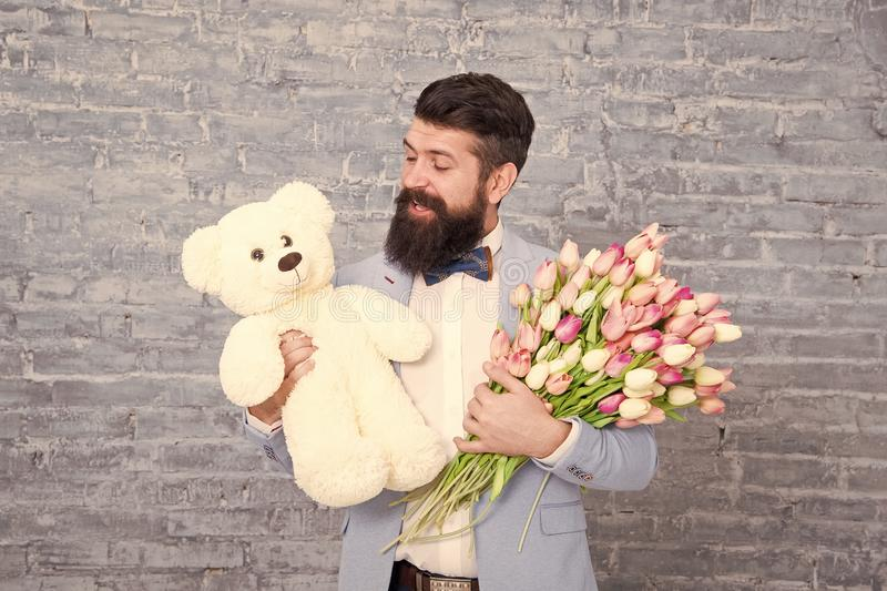 Romantic man with flowers and teddy bear. Romantic gift. Macho getting ready romantic date. Man wear blue tuxedo bow tie. Hold flowers bouquet. International royalty free stock image