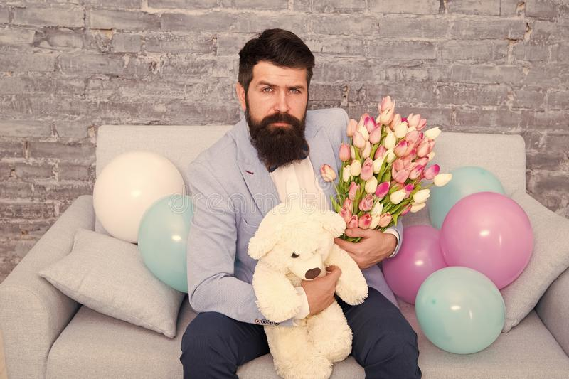 Romantic man with flowers and teddy bear sit on couch waiting girlfriend. Romantic gift. Macho getting ready romantic. Date. Man wear blue tuxedo bow tie hold royalty free stock photos