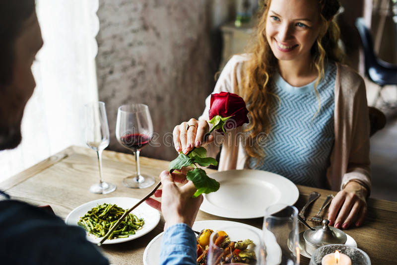 Romantic Man Giving a Rose to Woman on a Date royalty free stock photos