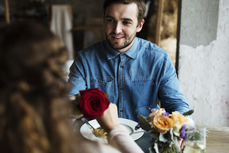 Romantic Man Giving a Rose to Woman on a Date stock photo