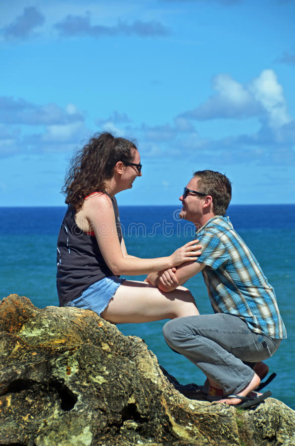 Romantic man proposing marriage on bended knees. A handsome young men with his gorgeous partner, very happy together sitting on top of a very high cliff at the royalty free stock photo