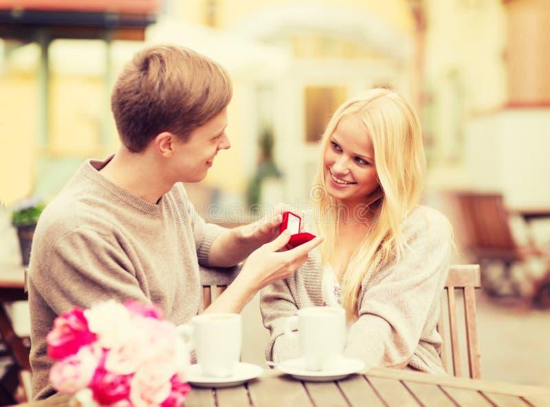 Romantic man proposing to beautiful woman stock image