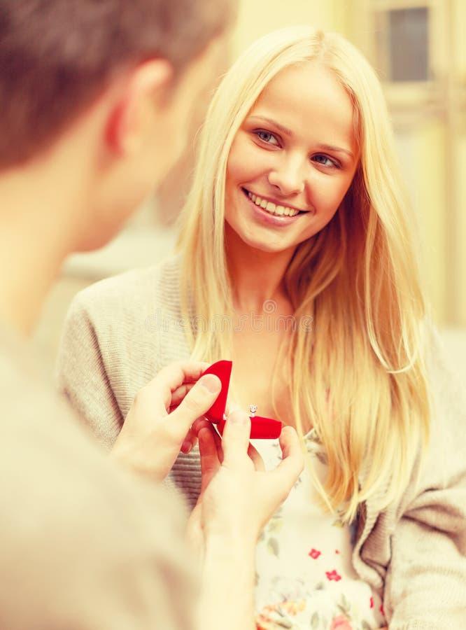 Romantic man proposing to beautiful woman stock photos