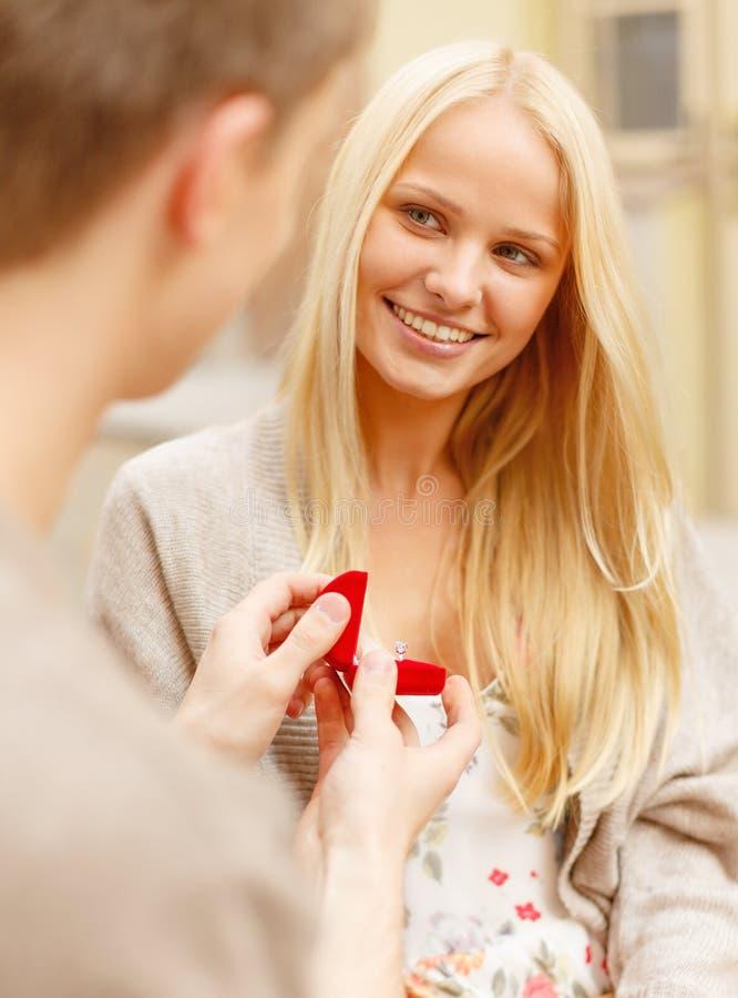 Romantic man proposing to beautiful woman royalty free stock photography
