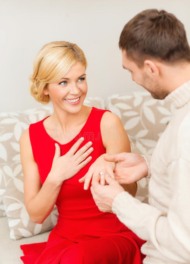 Romantic man proposing to a woman in red dress. Love, couple, relationship and dating concept - romantic men proposing to a women in red dress royalty free stock photo