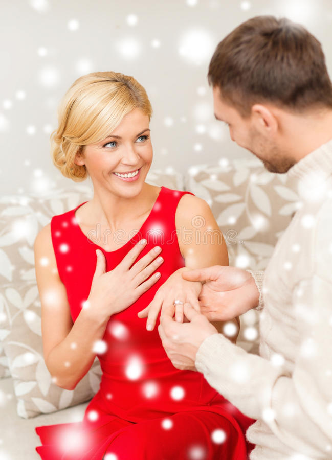Romantic man proposing to a woman in red dress. Love, couple, relationship and dating concept - romantic men proposing to a women in red dress stock photo