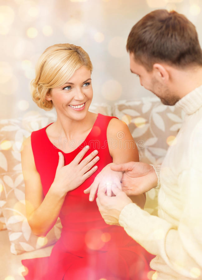 Romantic man proposing to a woman in red dress. Love, couple, relationship and dating concept - romantic men proposing to a women in red dress stock images