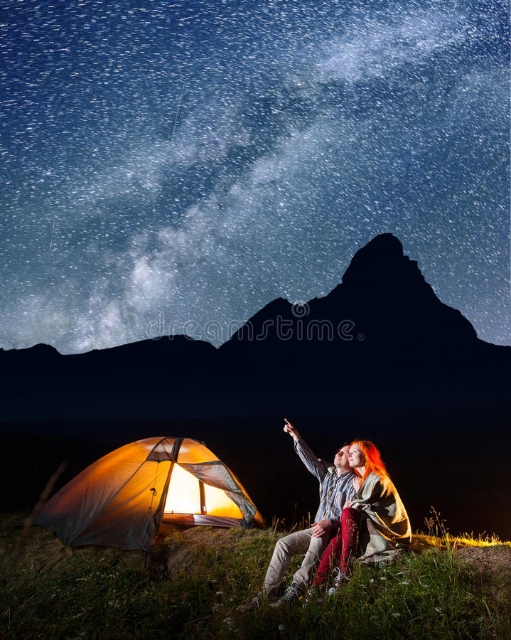 Romantic man showing his lover at the stars and Milky way in the night sky. Romantic men showing his lover at the stars and Milky way in the night sky. Pair royalty free stock photo