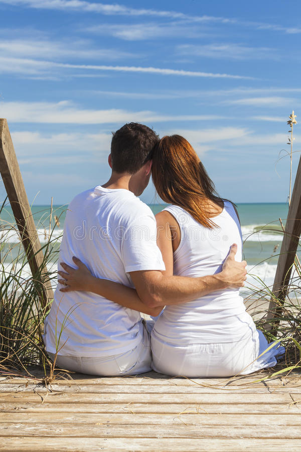 Romantic Man & Woman Couple Sitting Beach Steps. Rear view of romantic men & women couple sitting on wooden steps overlooking a beach royalty free stock photo