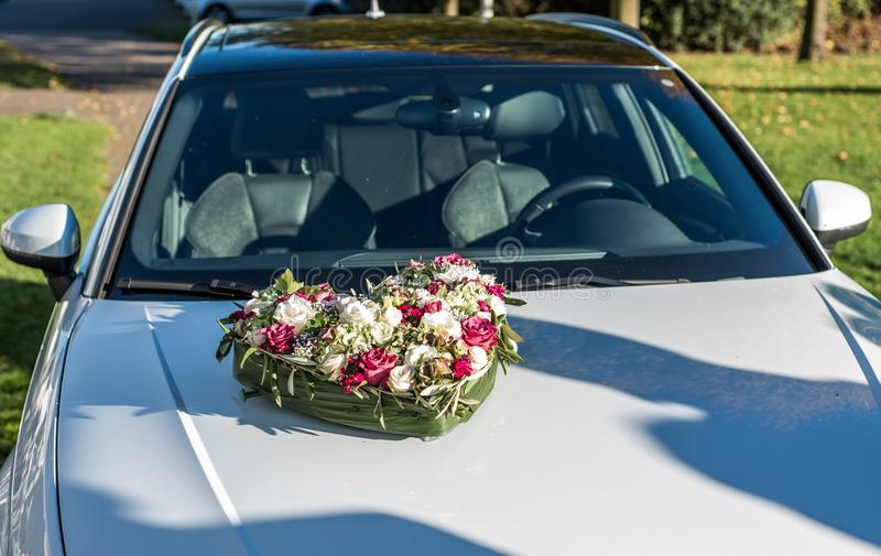 Romantic marriage couple wedding heart flower on car hood stock image