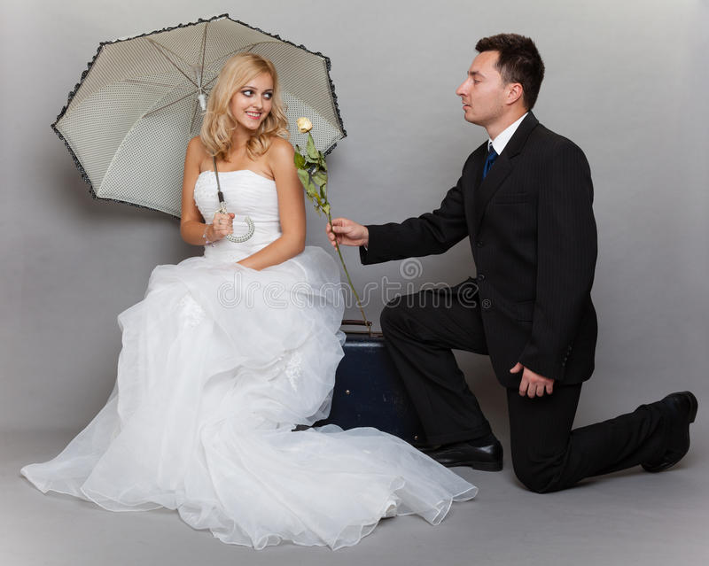 Romantic married couple bride and groom with rose. Wedding day. Portrait of romantic married couple blonde bride with umbrella and enamored groom giving a rose royalty free stock image
