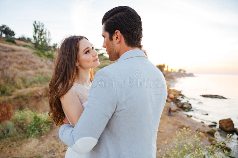 Romantic married couple standing on the beach stock photo