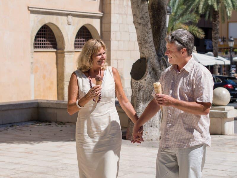 Romantic mature senior couple enjoying ice cream on a hot day royalty free stock photos