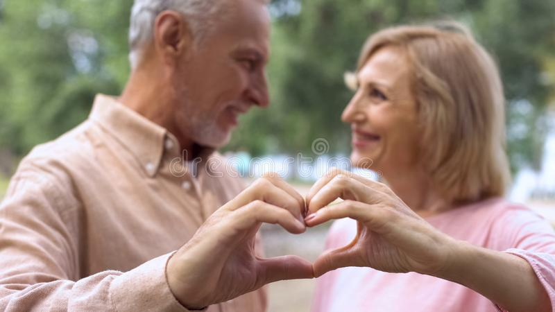 Romantic man and woman making heart sign by hands, looking each other with love royalty free stock photography