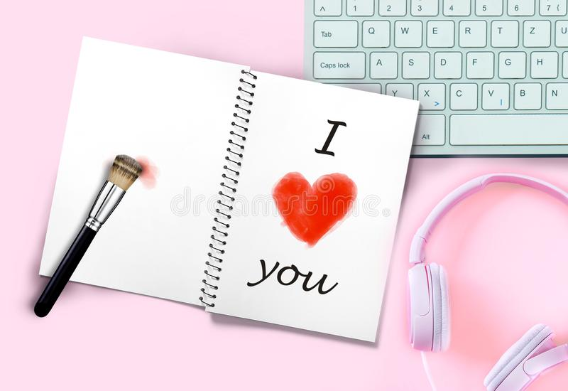 Romantic message I love you with red heart shape painted with makeup brush in notepad opened on pink desk next to keyboard and. Romantic message I love you with stock image