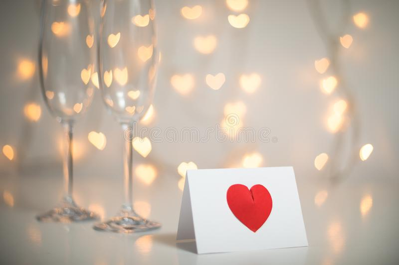 Romantic message note with red 3d heart on it, and champagne with glasses and fairy light strings with heart bokeh in the backgrou stock photos