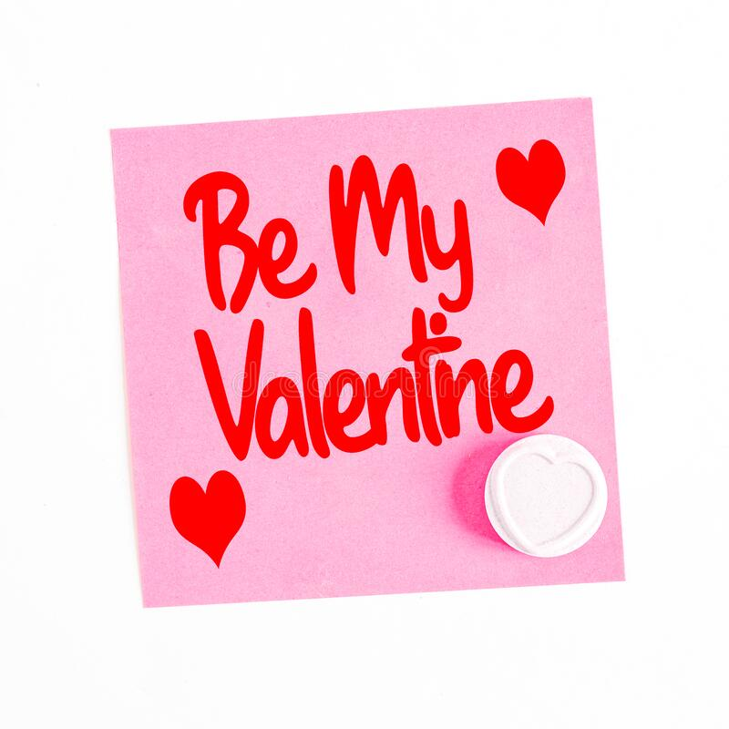 Romantic message on a sticky note saying Be My Valentine with a Love Hearts candy. A romantic message left on a pink sticky note with the phrase Be My Valentine stock images