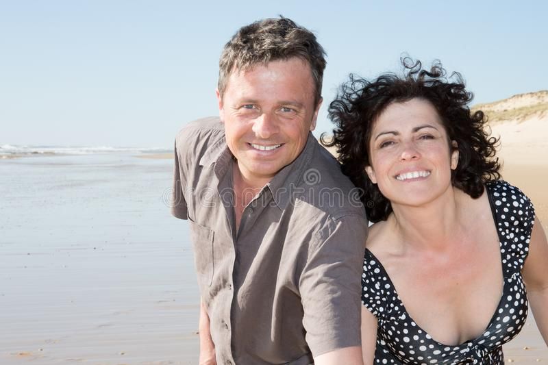 Romantic Middle Aged Couple Enjoying play and love on the Beach royalty free stock image