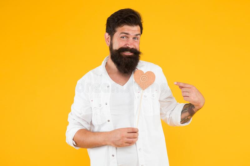 Romantic mood. Handsome macho with long beard. Fall in love. Happy valentines day. Bearded man holding heart. Hipster stock photos