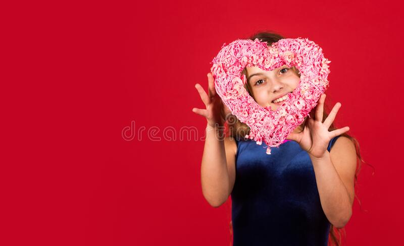 Romantic mood. Happy child hold heart red background. Little girl with pink heart. Heart shaped decor valentines day. Holiday of love and care. Feeling loved royalty free stock photos