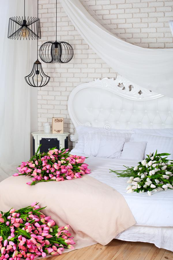 Romantic morning in a chic bedroom. A large bouquet of pink tulips lie on a white bed. Classic bedroom design. Brick white wall. M. Any unusual geometric lamps royalty free stock image