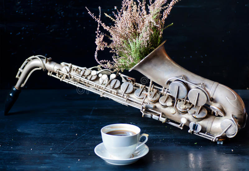 Romantic morning with coffee cup and flowers in saxophone. Romantic morning with coffee cup and flowers in old pipe of saxophone royalty free stock photo