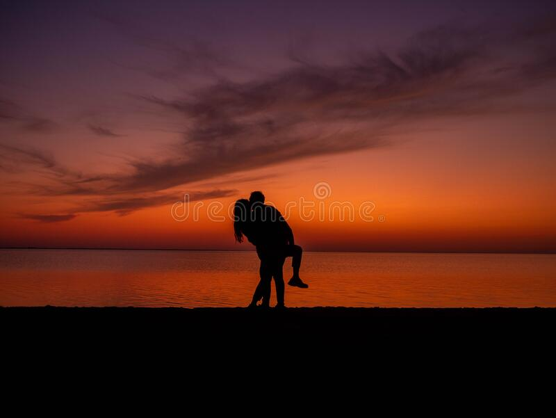 Romantic couple hugging and kissing during sunset. Romantic multi-ethnic couple admires the scenic sunset over the sea. Holding hands, rear view stock photo
