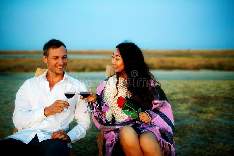 Romantic multi-ethnic couple admires the scenic sunset over the sea. Young couple drink wine on the beach, young man gives rose to royalty free stock photography
