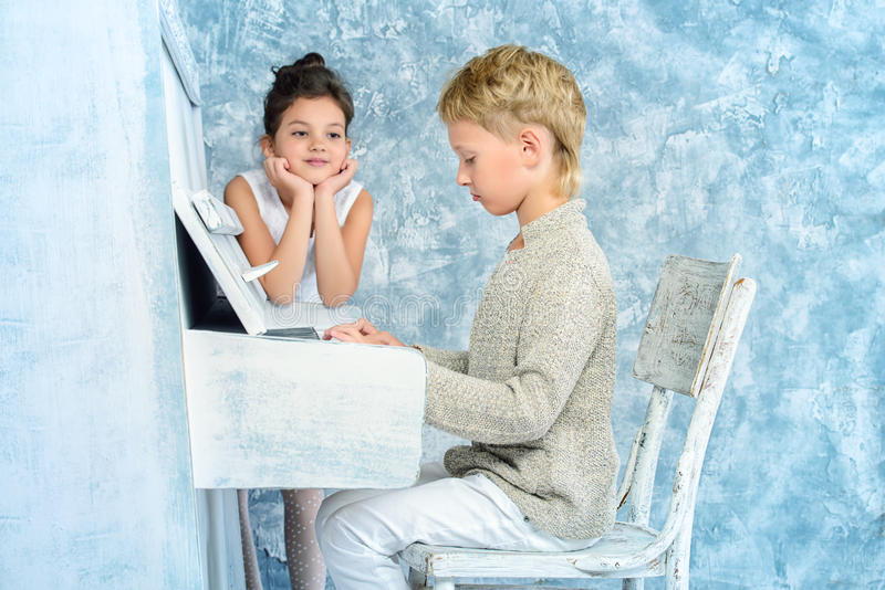 Romantic music. Romantic children playing the white piano. Music and art concept. Vintage, retro style royalty free stock image