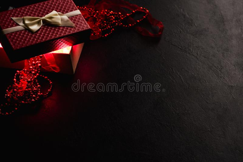 Romantic mystery red gift box present dark decor. Romantic mystery red light coming gift box. atmospheric and enigmatic present on dark background with jewelry royalty free stock image