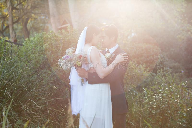 Romantic newlywed couple with eyes closed embracing in park royalty free stock photo