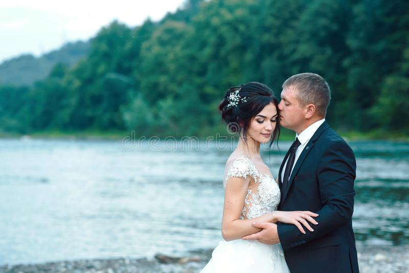 Romantic newlywed couple hugging near blue lake, sensual groom embracing gorgeous bride from behind near river. Wedding day for ma. Romantic newlywed couple stock photos