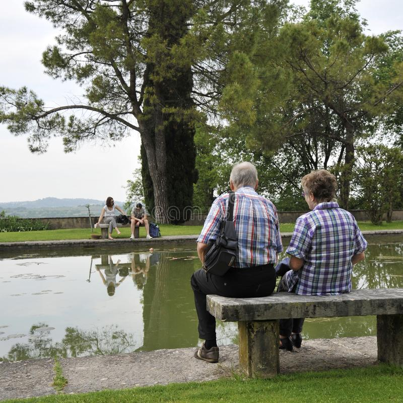 Romantic old and young couples sitting on park bench by lake. royalty free stock image
