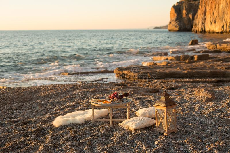 Romantic picnic with wine and cheese by seaside royalty free stock photography