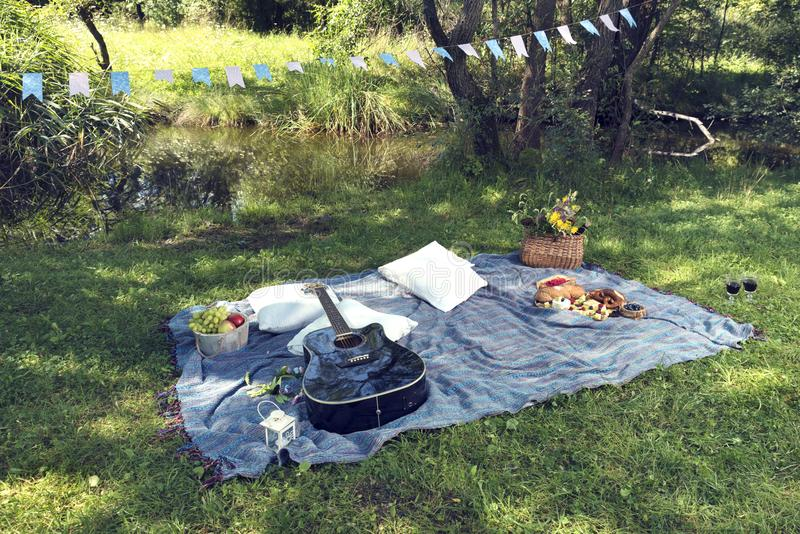 Romantic picnic next to a pond with fresh food and guitar. Selective focus stock photo