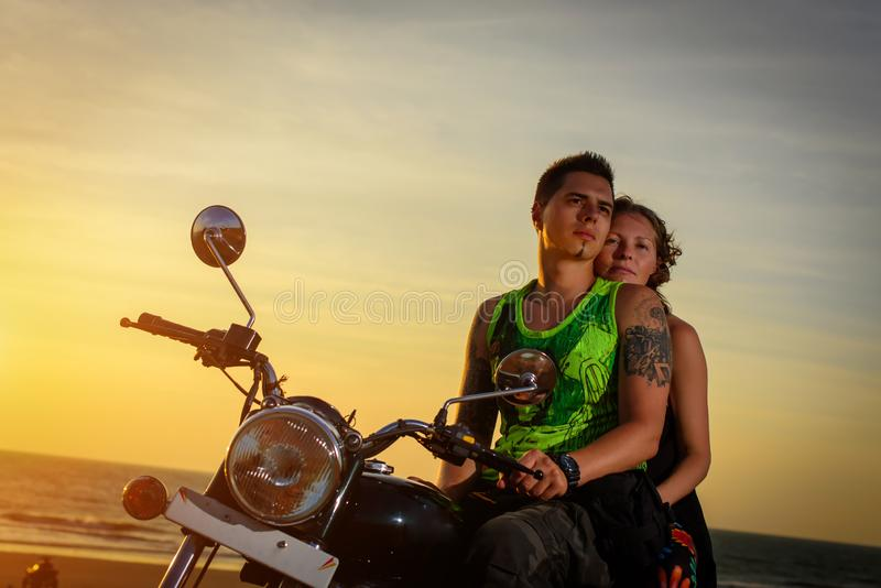 Romantic picture with a couple of beautiful stylish bikers at sunset. Handsome guy with tatoo and young sexy woman enjoy royalty free stock images