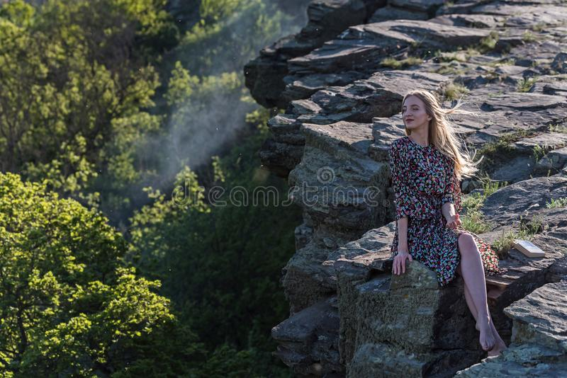 Beautiful girl in dress sits on rock in nature royalty free stock photo