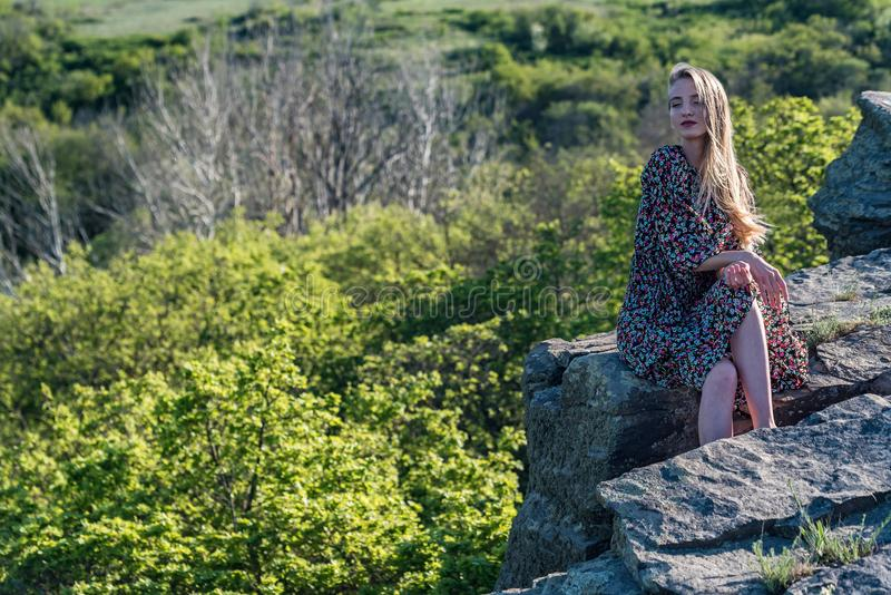 Beautiful girl in dress sits on rock in nature stock photos