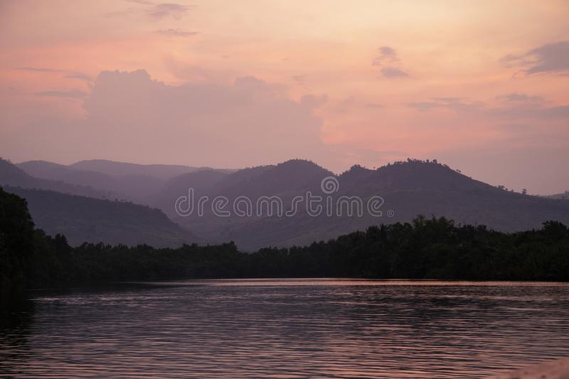 Romantic pink sunset with still lake and distant mountains. Beautiful asian landscape photo. Fresh water river stock photos