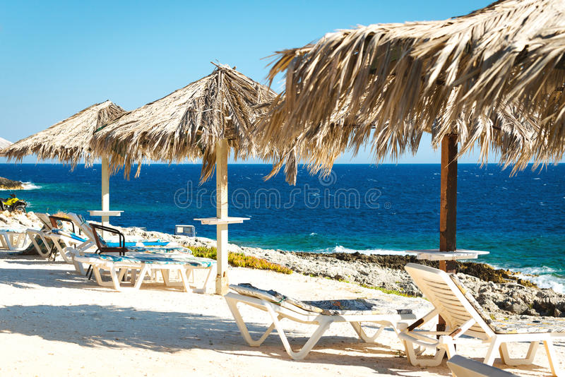 Romantic place near the sea. Summertime vacation holidays background. Sunny beach with sunbeds under umbrellas royalty free stock images