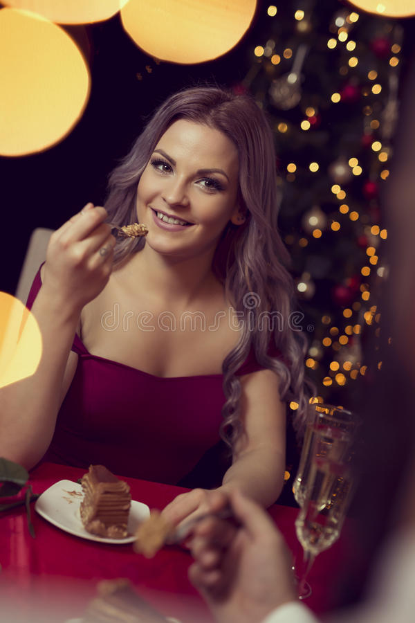 Romantic pleasures. Beautiful young couple having a conversation on a romantic Christmas dinner, drinking wine and eating cake stock image