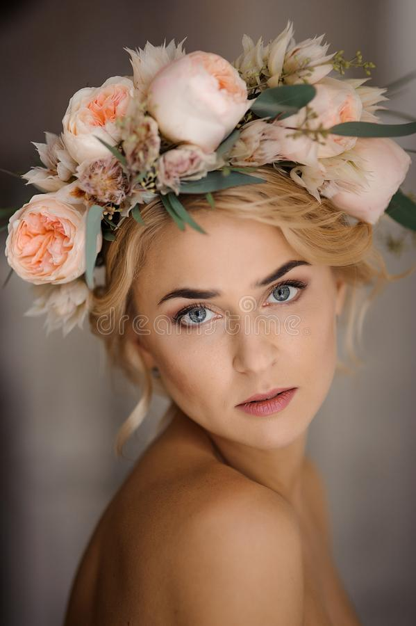 Portrait of the attractive topless blonde woman in a tender floral wreath. Romantic portrait of the attractive topless blonde woman in a tender floral wreath stock photography