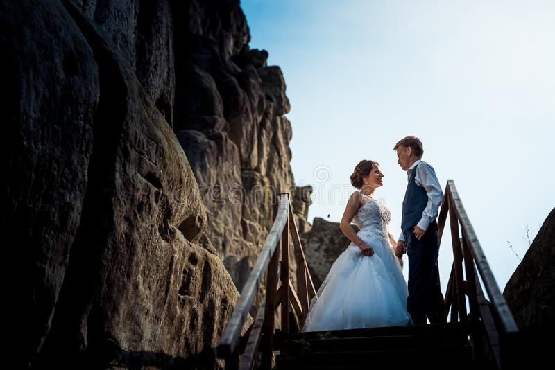 Romantic portrait of the beautiful smiling newlyweds holding hands near the wooden staircases near the rock. stock photography