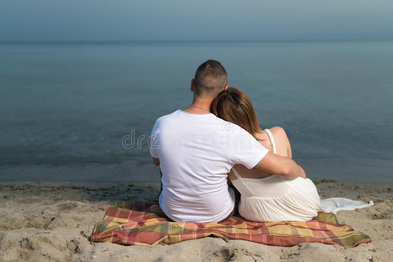 Romantic portrait of couple in love hugs sitting on the beach at the sunset royalty free stock photos