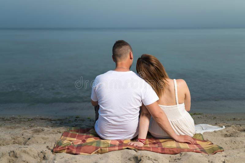 Romantic portrait of couple in love hugs sitting on the beach at the sunset royalty free stock images