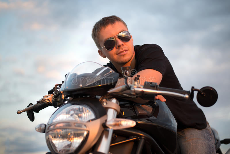 Romantic portrait handsome biker man in sunglasses. Sits on a bike on a sunset near lake and city stock photo