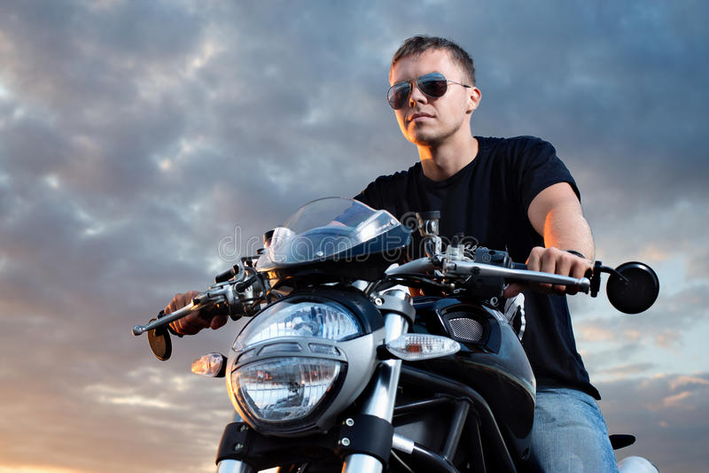 Romantic portrait handsome biker man in sunglasses. Sits on a bike on a sunset near lake and city royalty free stock photo