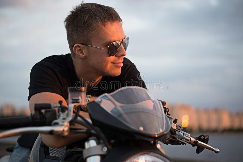 Romantic portrait handsome biker man in sunglasses. Sits on a bike on a sunset near lake and city stock photography