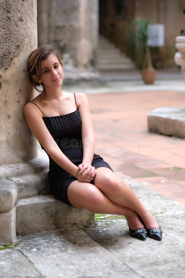 Romantic portrait of a pretty hispanic teenage girl. Leaning on an old stone column stock photography